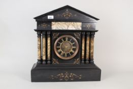 A substantial black marble mantel clock with gilt painted decoration and pale marble columns