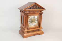 An Edwardian carved walnut cased mantel clock with brass and silvered dial and striking movement