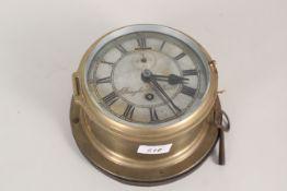 A brass ships clock on an oak base,