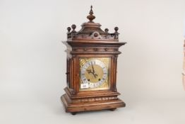 A carved oak cased brass and silver dialled mantel clock with construction sketches