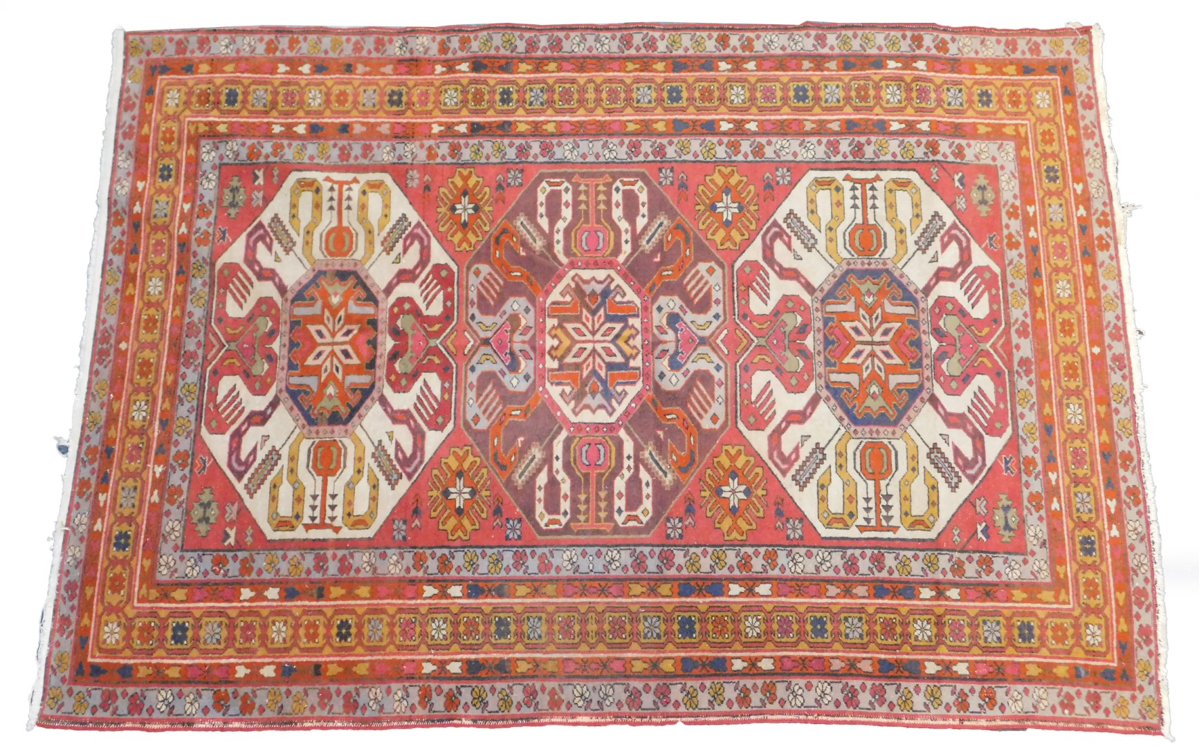 Lot 14 - An Azerbaijan Kazak rug, with three central medallions on a red ground, enclosed by triple borders