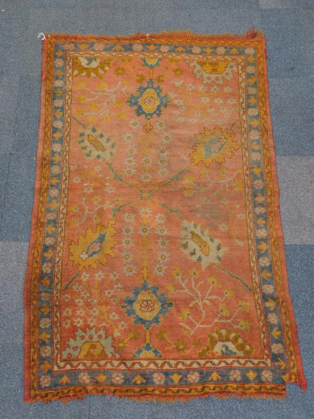 Lot 12 - An Oushak rug, with multi medallion centre on a madder ground, with blue banded triple border, 200cm