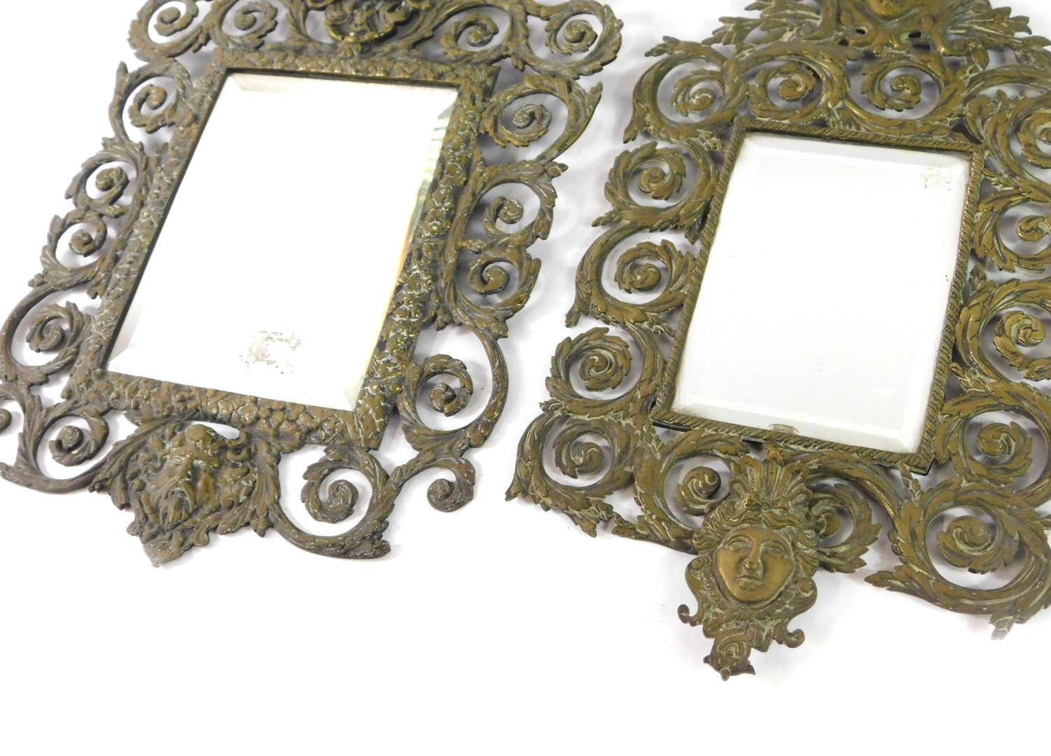 Lot 48 - Four 19thC brass strut mirrors, struts lacking, cast with classical masks and foliate scrolls, three