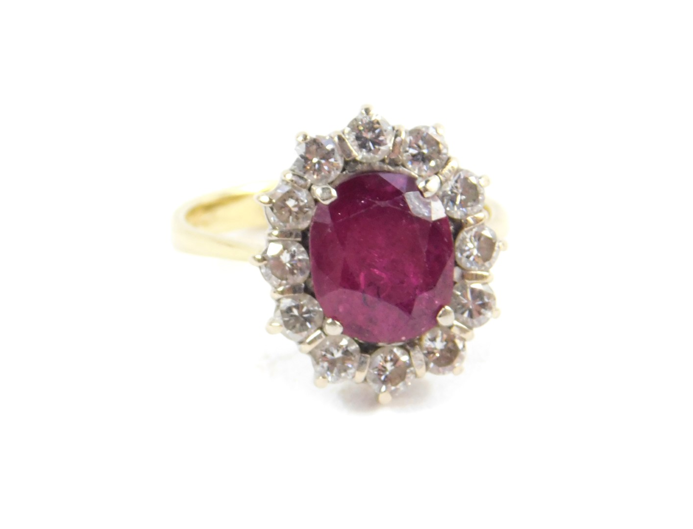 Lot 3 - An 18ct ruby and diamond ring, the oval cut ruby, approx 3.5cts, in a surround of twelve diamonds,