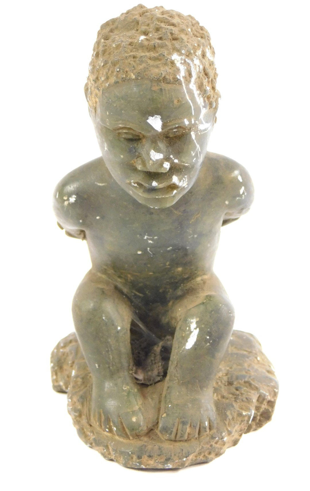 Lot 49 - A Zimbabwean hardstone sculpture of a man, modelled naked seated on the ground with his arms wrapped