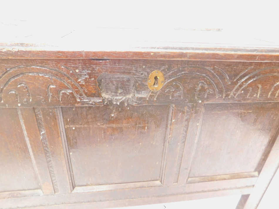 Lot 764 - A late 17th/early 18thC oak coffer, with a panelled top above a frieze carve with arches, on stiles,