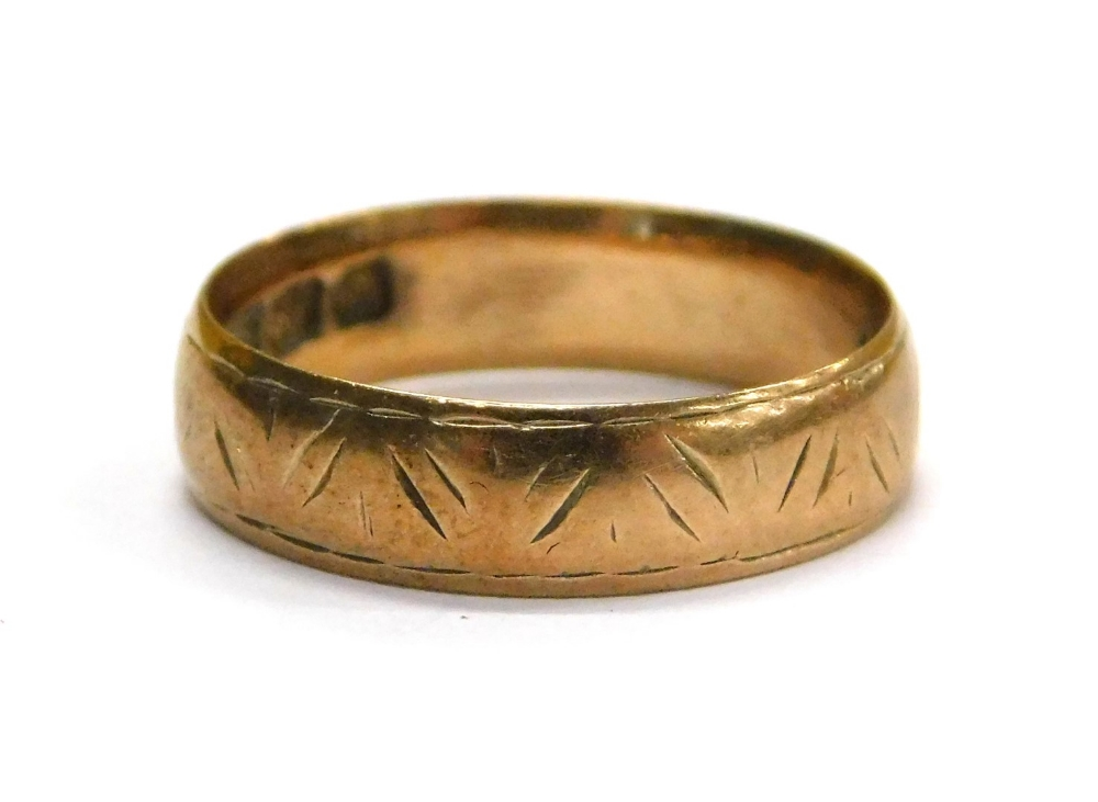 Lot 73 - A 9ct gold wedding band, with rubbed etched design, ring size J, 2g all in.
