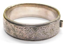 A hinged bangle, with foliate scroll decoration on one side and outer border, with single lion