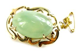 An oval brooch, with central pale green jadeite type stone, the scroll design frame with four claw