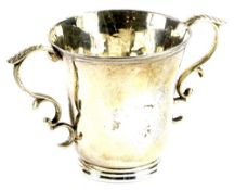 A continental silver coloured metal two handled cup, of tapering form with a moulded rim and
