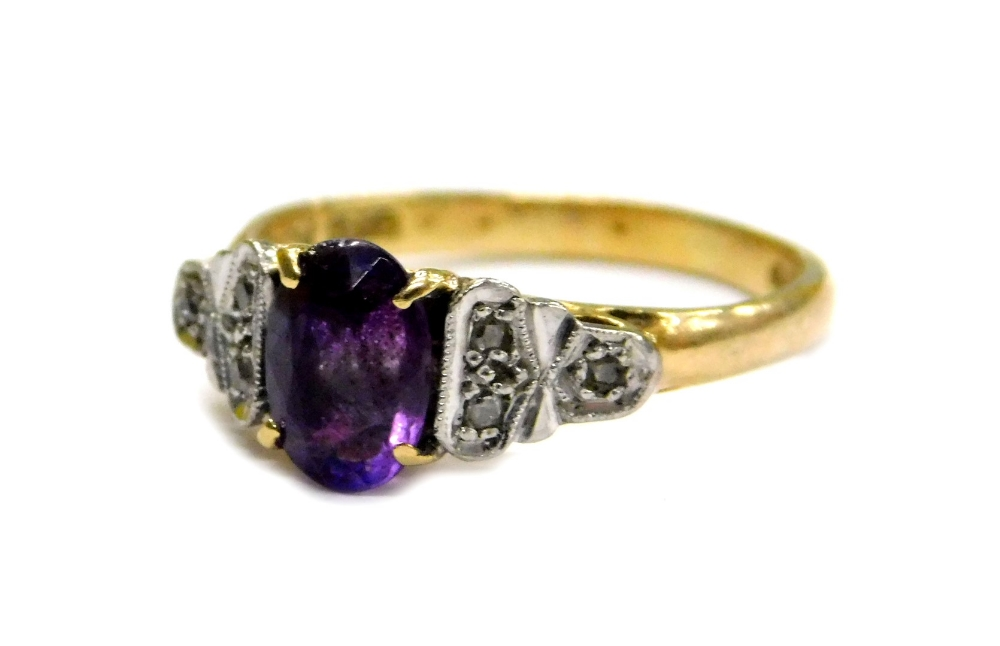 Lot 69 - An 18ct gold and platinum amethyst and diamond dress ring, set with oval cut amethyst stone in