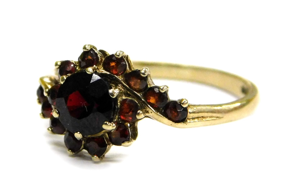 Lot 67 - A 9ct gold garnet set dress ring, of twist design with large central stone, flanked by smaller stone
