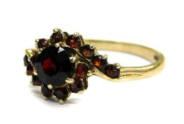 A 9ct gold garnet set dress ring, of twist design with large central stone, flanked by smaller stone