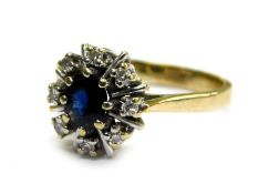A 9ct gold cluster ring, set with central oval cut sapphire in gold eight claw setting, surrounded
