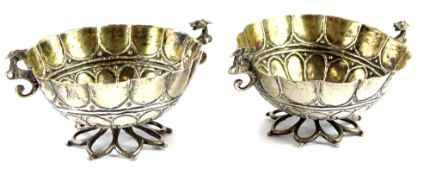 A pair of continental white metal salts, each with a gilt interior, cast as a flowerhead, etc.,
