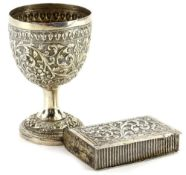 Two items of Eastern white metal, an egg cup embossed and chased with scrolls, flowers, etc. on a