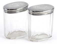 A pair of Victorian facetted oval cut glass dressing table jars, each with an engine turned lid with