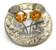 A silver plated thistle brooch, set with two orange coloured costume stones, 4cm wide.