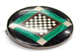 An oval malachite and black onyx set brooch, with central diamond hatched decoration, in a white
