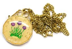 A modern coin pendant and chain, with a three pence piece enamel decorated pendant, in gold plated