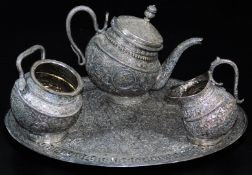 An early 20thC Indian four piece service, comprising shaped tea pot, sugar bowl and jug on an oval