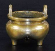 A Chinese bronze tripod censer, with bulbous body and twisted loop handles, six character Xuande