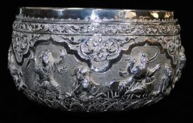 An early 20thC Indian ceremonial bowl, heavily repousse decorated with figures scrolls and