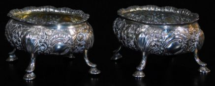 A pair of late 18thC silver salts, of oval form, heavily repousse decorated with a repeat floral