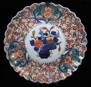 A Japanese Imari charger, of shaped floral form, centred with a vase of flowers, with an outer