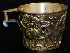 A 20thC gilt coloured cup, with compressed cylindrical handle, repousse decorated with buffalo and