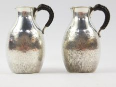 A pair of Japanese silver jugs, with leather bound handles, of bulbous form, with textured