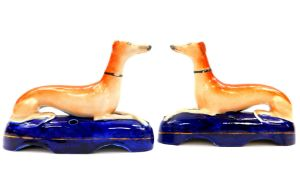 A pair of Staffordshire 19thC pottery greyhound ink wells, each modelled in recumbent pose on a blue