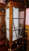 A mid 20thC oak china cabinet, raised on cabriole legs, 117cm high, 56cm wide, 31cm deep.