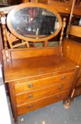 An oak early 20thC dressing chest, with oval swing mirror above three drawers, 146cm high, 91cm