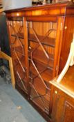 A reproduction mahogany glazed bookcase, with astral glazed doors raised on a plinth base, 153cm
