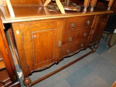 A 20thC oak sideboard, with carved back rail above three central drawers flanked by cupboards, 117cm