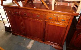 A reproduction cherry wood sideboard, with six drawers over three cupboard doors, 106cm high,