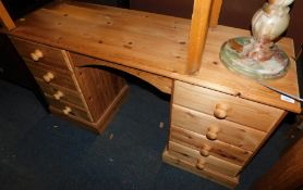 A waxed pine desk or dressing table of eight drawers, 77cm high, 130cm wide, 43cm deep.