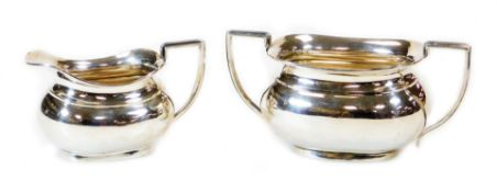 A George V silver two handled sugar bowl, 10cm high and milk jug each with angular handles of cape f