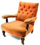 A late 19thC low armchair, with studded back and arms and overstuffed seat in peach material, with t