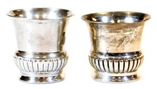 A matched pair of early 20thC silver vases, each of campana form, partially gadrooned on circular fe