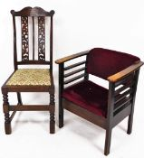 A 1920's oak occasional chair, with overstuffed back and seat, in crimson material, on chamfered sti