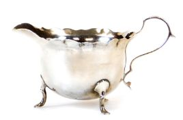 A George V silver cream jug, with flared rim, acanthus capped ear handle and triple hoof feet, Londo