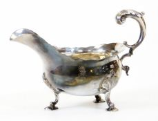 A George III silver sauce boat, with flared rim, flying acanthus scroll handle and leaf capped tripl