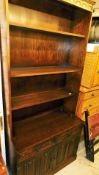 A 20thC oak linen fold open bookcase, 203cm high, above two drawers and double cupboard on a block b