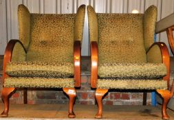 A pair of Parker Knoll style wing armchair, in scroll material on green ground, 99cm high.