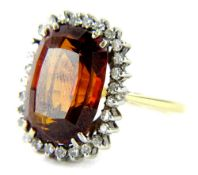 An 18ct gold garnet and diamond dress ring, with central faceted 15.8mm x 12mm x 8.2mm, surrounded