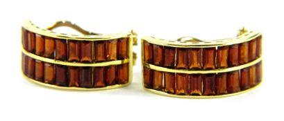 A pair of 18ct gold garnet set half hoop earrings, each set with two rows of baguette cut garnets,