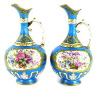 A pair of 19thC Sevres style ewers, each painted with baskets of flowers within an elaborate