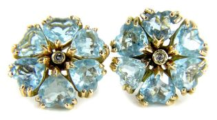 A pair of aquamarine and diamond earrings, each set in a floral cluster with central diamond
